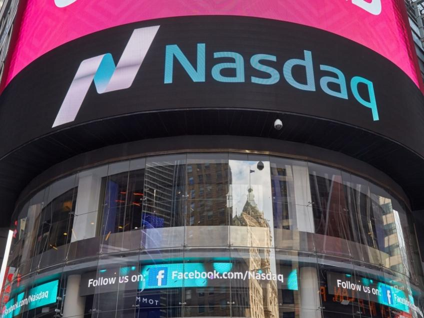 Wall St. ekes out gains as Nasdaq hits record high on stimulus hopes
